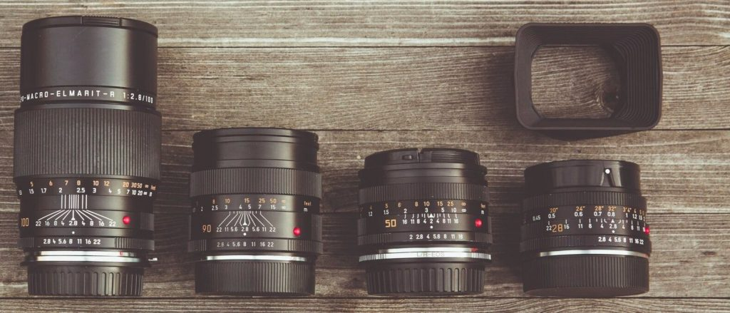 A few manual focus lenses sitting on a table.